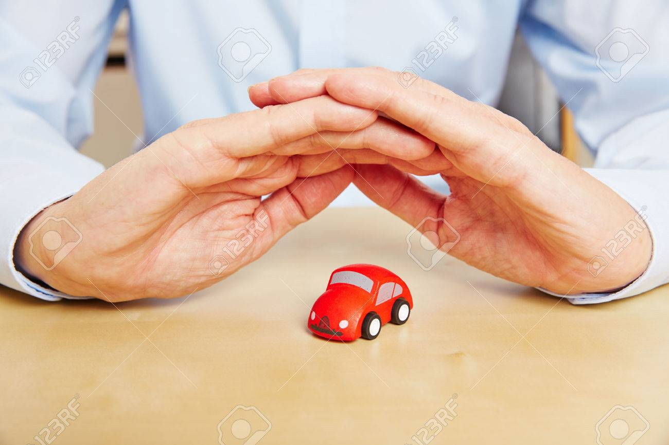 Car insurance with hands over red vehicle as a symbol Stock Photo - 53562628