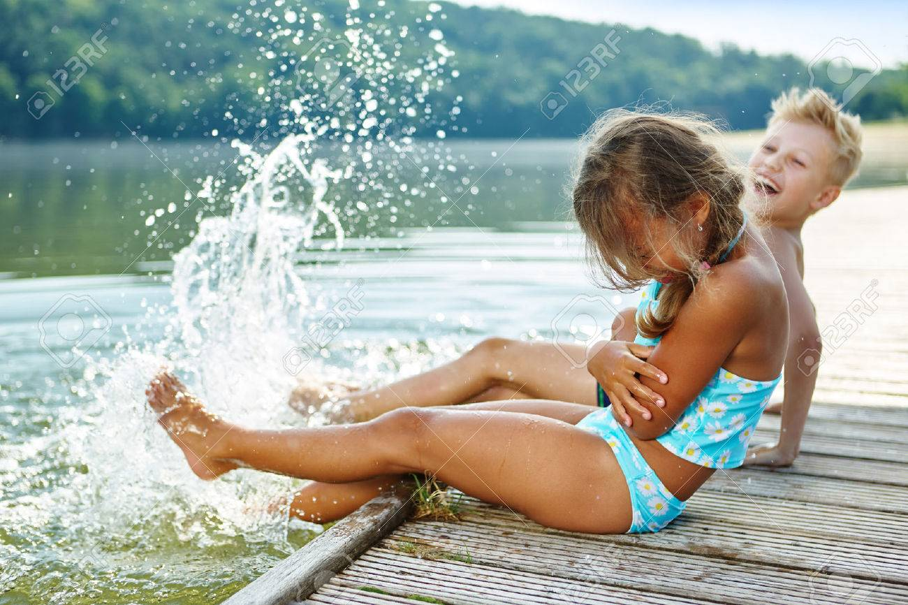 Two kids splashing water with their feet in summer Banque d'images - 52994497