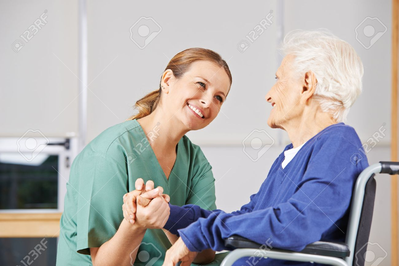 Happy geriatric nurse holding hands with senior woman in a wheelchair - 52996461