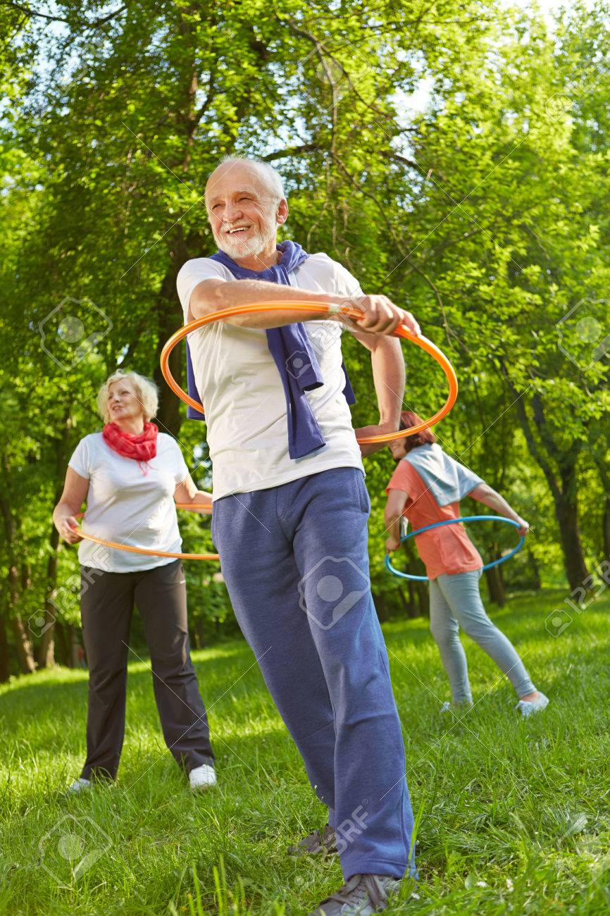 Senior group with hoops in a fitness class exercising in nature in a garden - 55605690