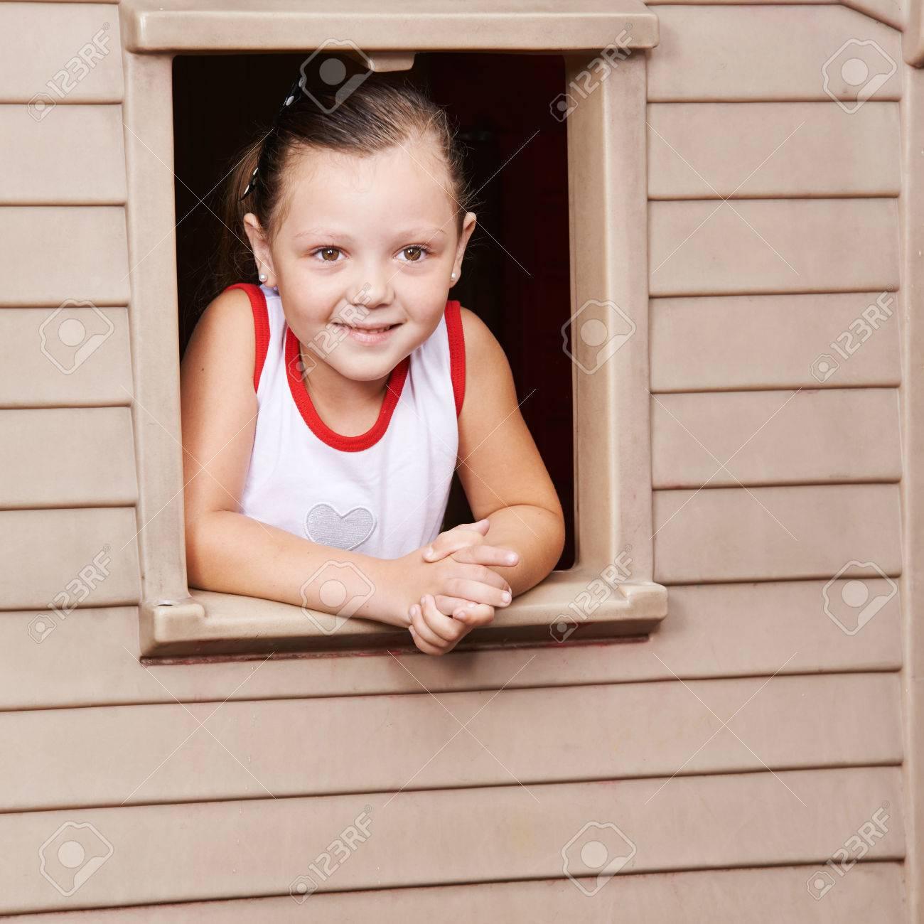 nia feliz mirando por la ventana de una casa de juegos en el jardn de infancia