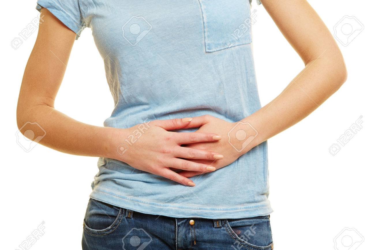 Young woman with bellyache holding hands on her stomach Standard-Bild - 55605835