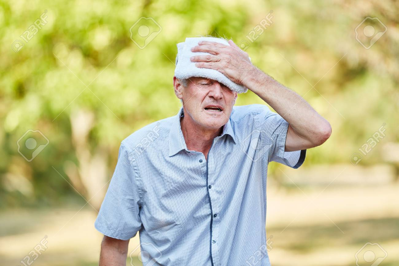 Senior man with bad circulation cools his head with wet cloth Standard-Bild - 55605962