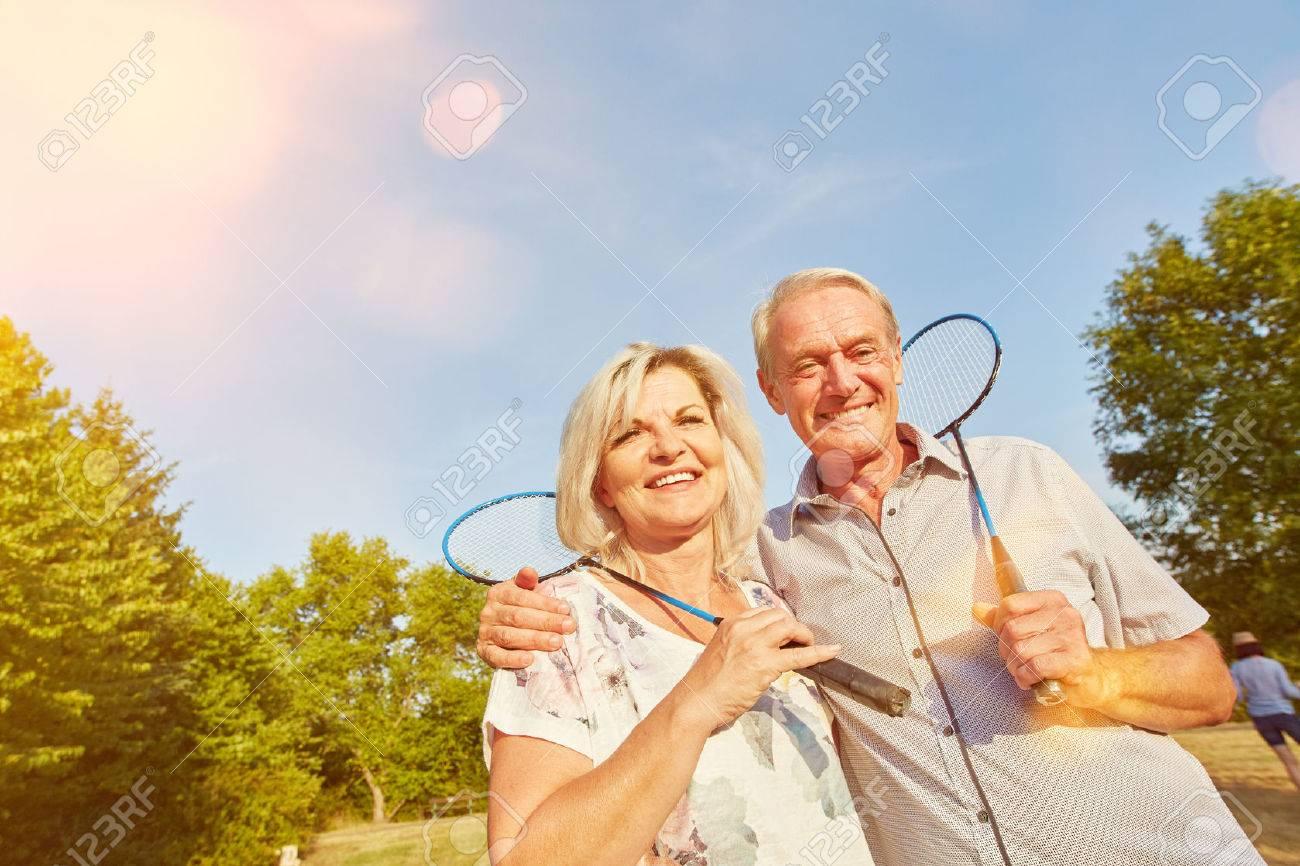 Happy senior couple while playing badminton in summer Standard-Bild - 55605966