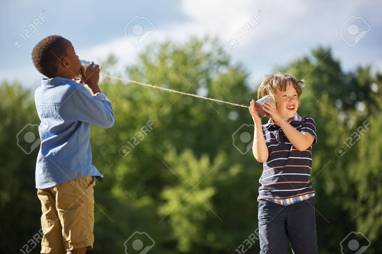 Two boys play tin can telephone with each other at the park - 55606031