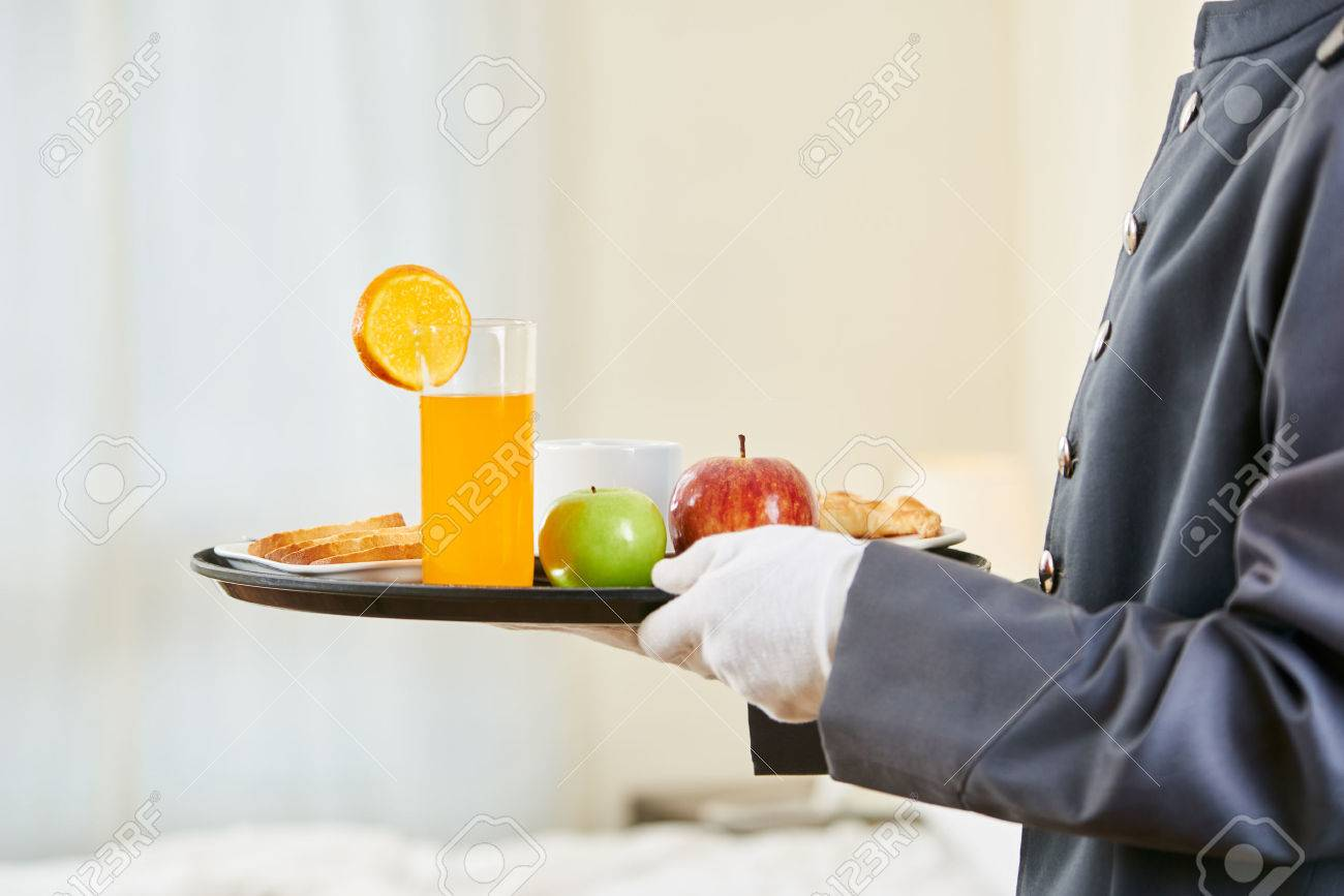 Room service bringing healthy breakfast with orange juice and fruits - 60524209