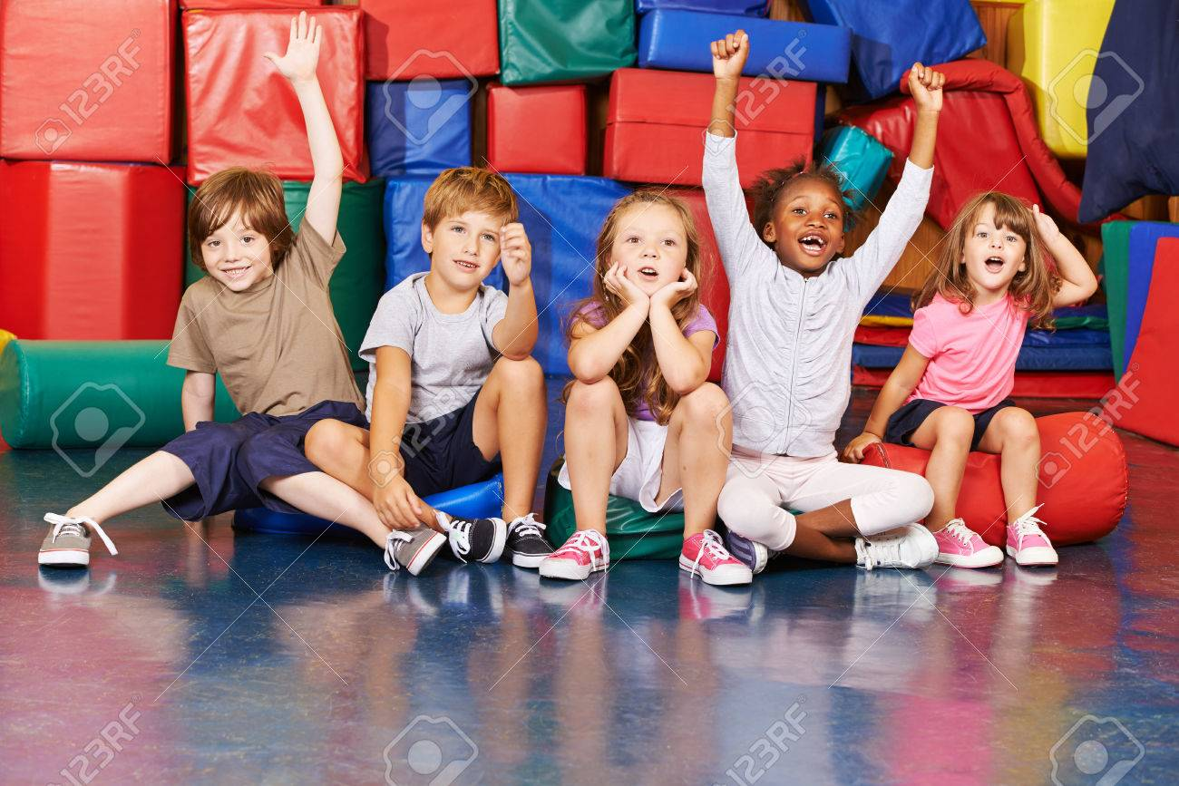 Children cheering together after victory in gym of a pre school - 61079666