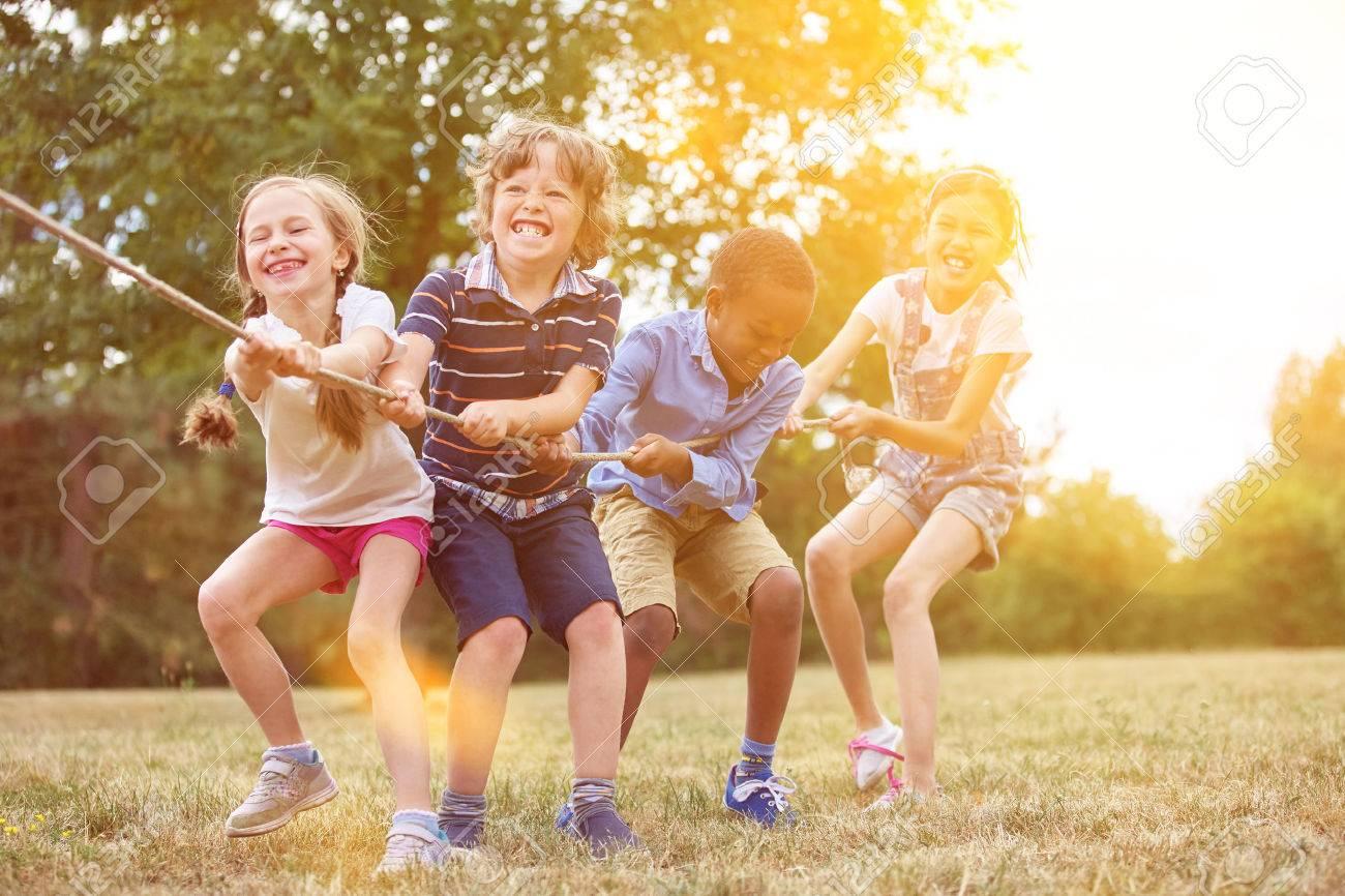 Kids playing tug of war at the park Standard-Bild - 61693660