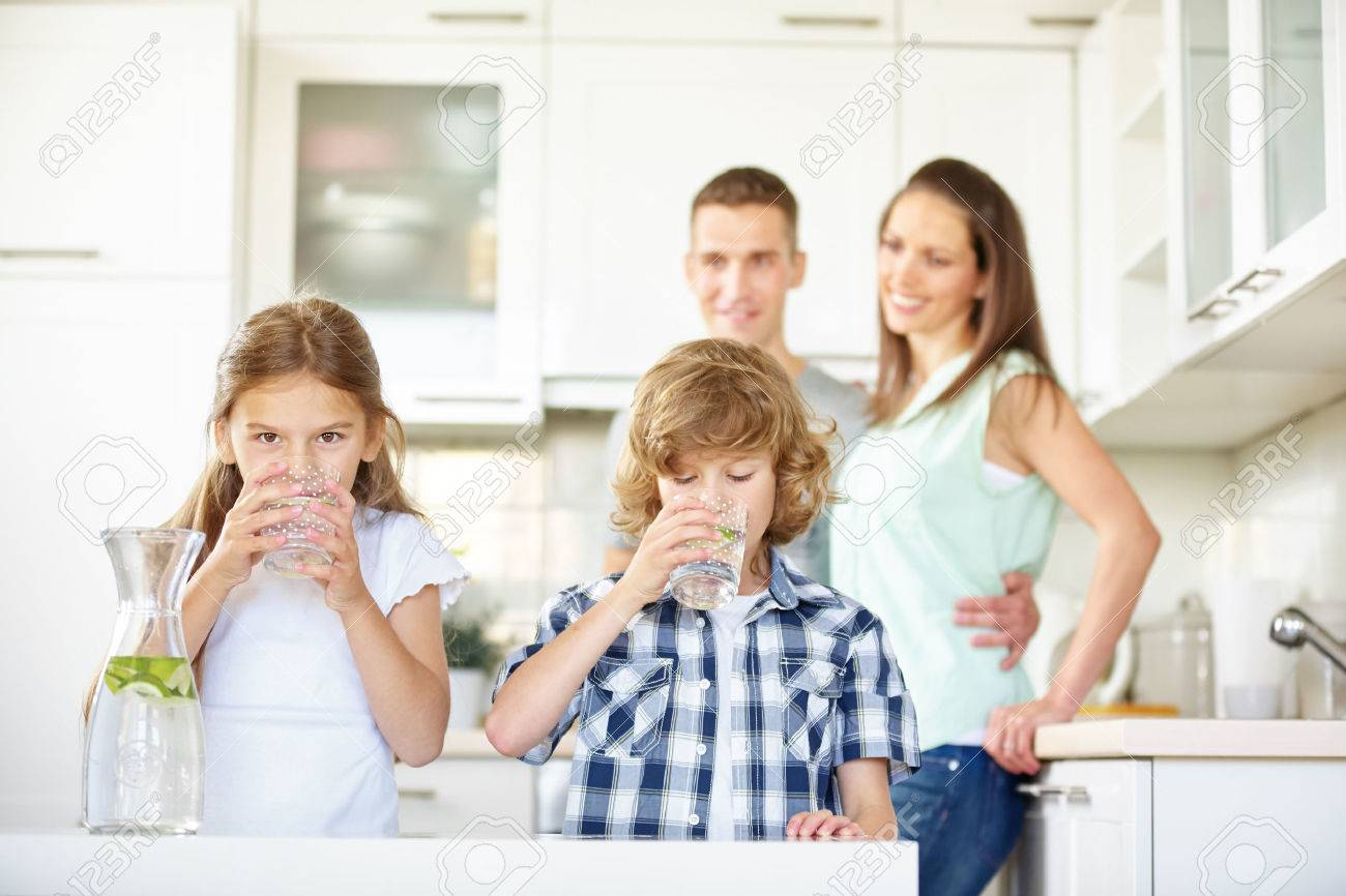 Boy and girl drinking water with lime in the kitchen while the parents are watching Standard-Bild - 66702587