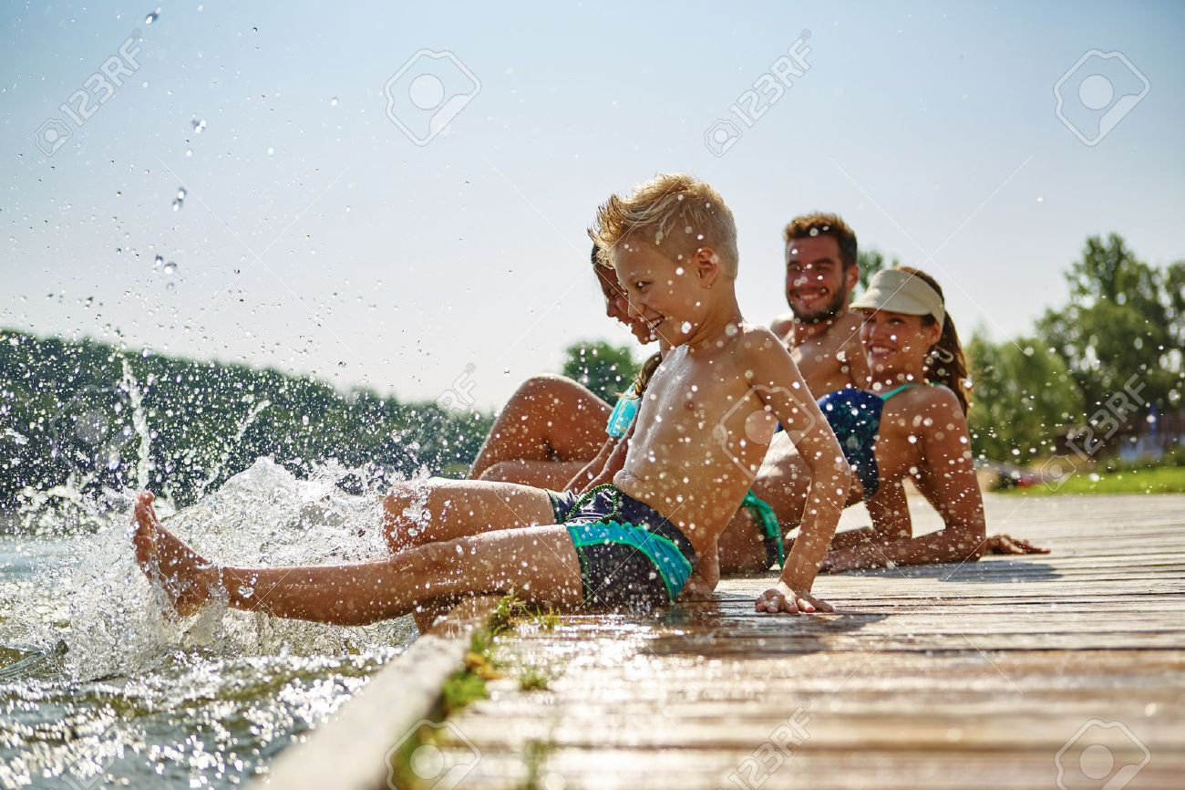 Happy family at a lake having fun and splashing water in summer Banque d'images - 70588460