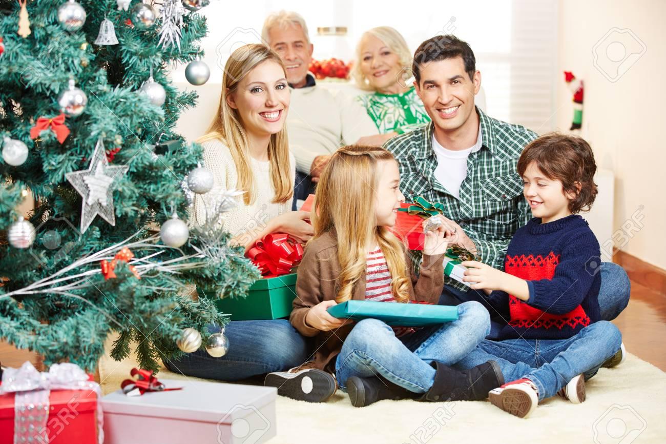 Glückliche Familie Mit Großeltern , Die Geschenk Am Weihnachtsabend ...