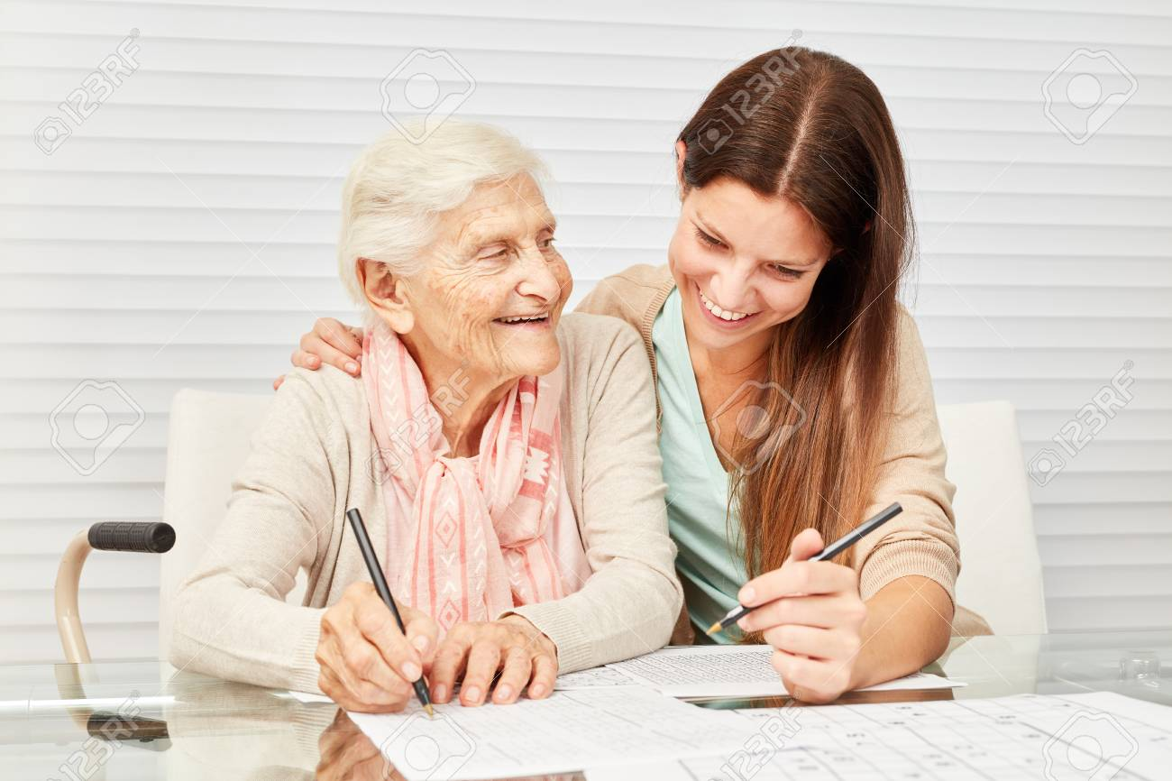 Girls as a caring grandson and senior together solve puzzles in retirement home - 93942485