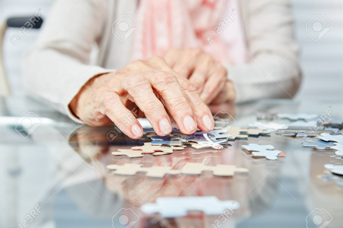 Hands of seniors playing puzzle as dementia prevention in retirement home - 103952267