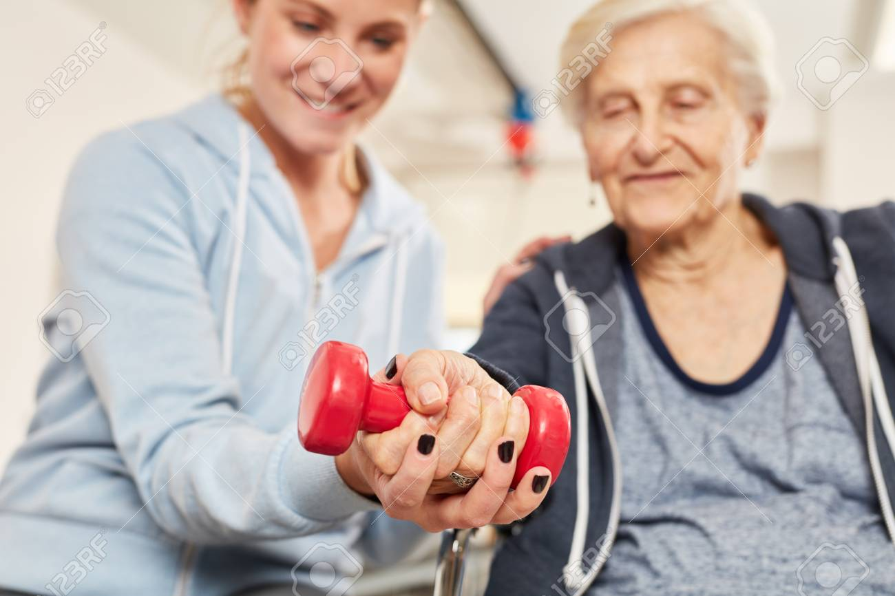Physiotherapist helps elderly woman with healthy dumbbell training in rehab - 115105998