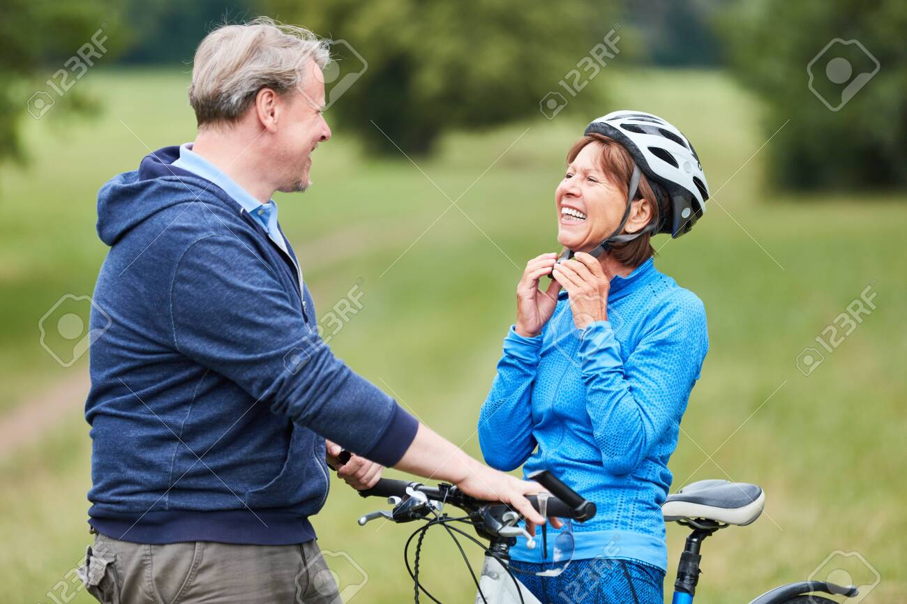 Active senior woman puts on a bicycle helmet with partner before the bike ride - 121179148
