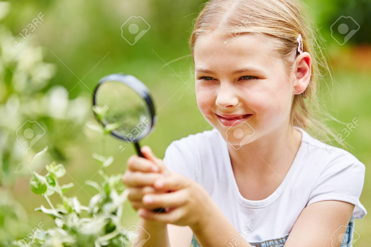 Girl researches with magnifying glass in garden and explores nature with curiosity - 120086019