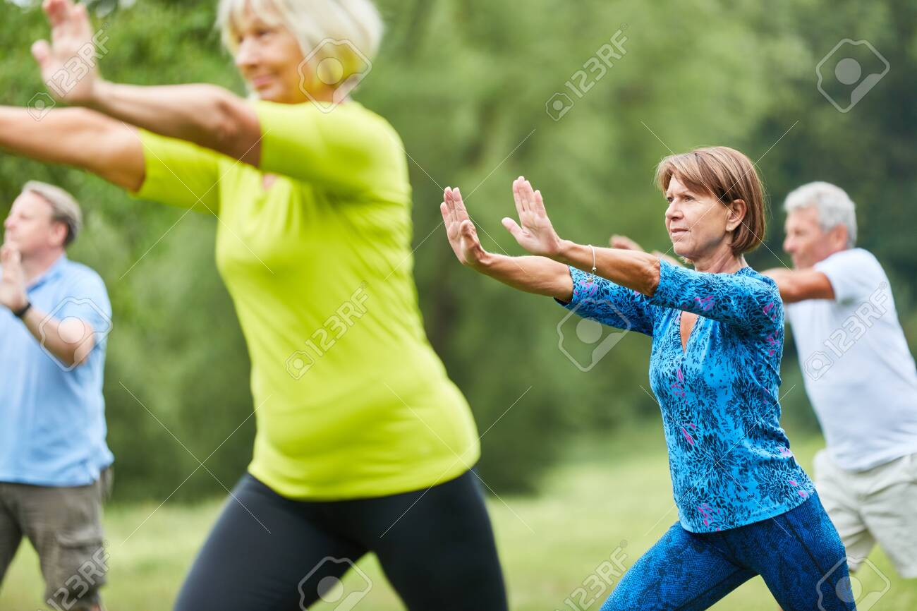 Seniors do Qi Gong or Tai Chi exercise for relaxation and health - 127705576