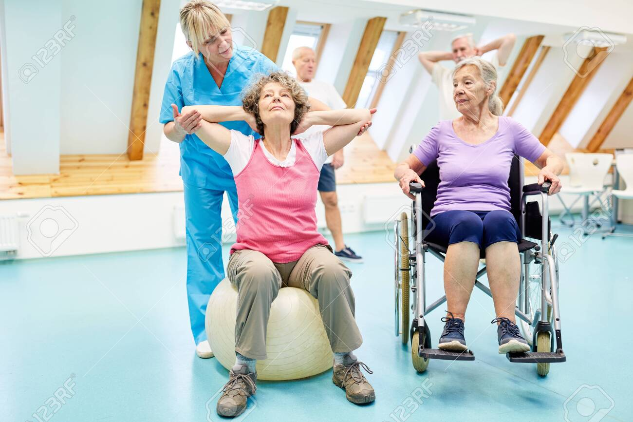 Physiotherapist helps seniors with rehab exercises in the physiotherapy