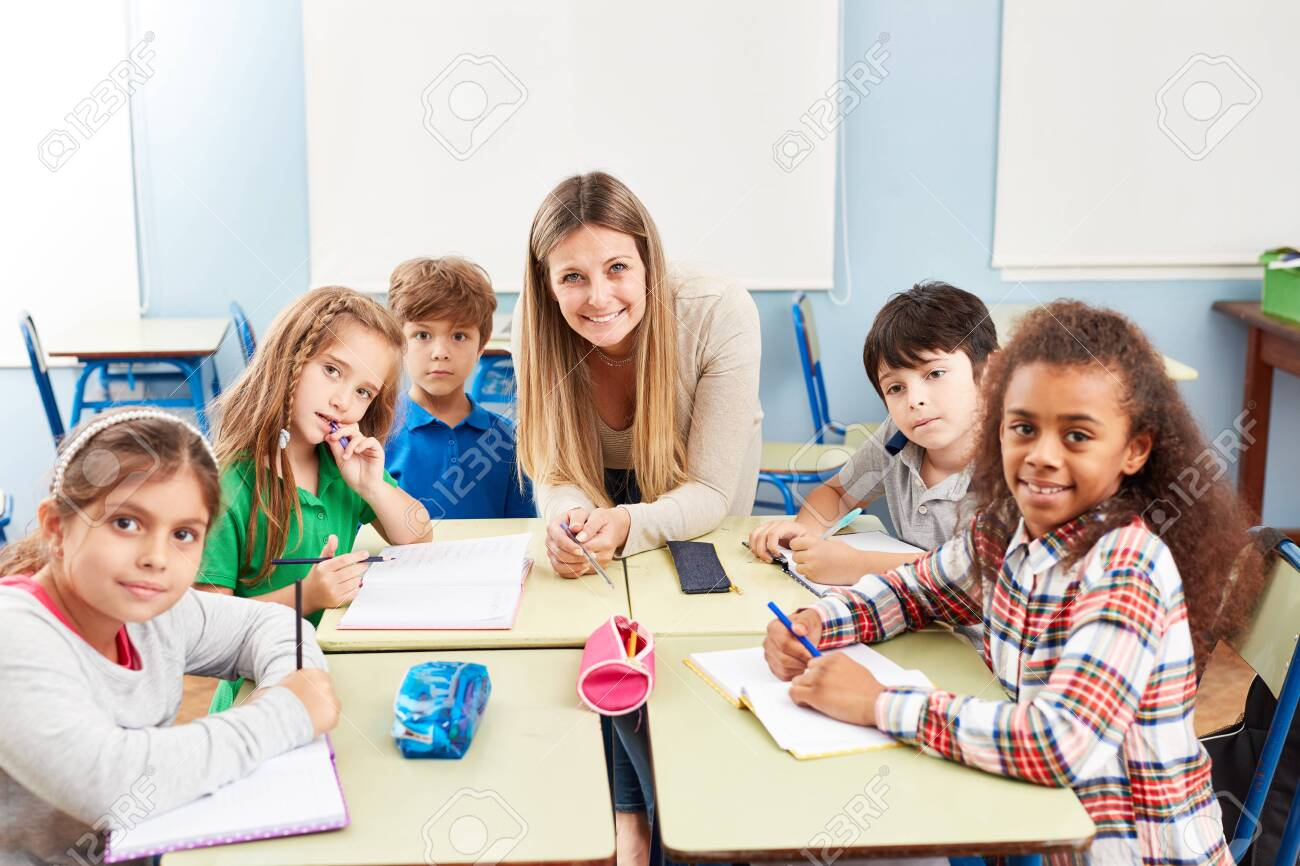 Group of multicultural elementary students in tutoring lessons with teacher - 129369456