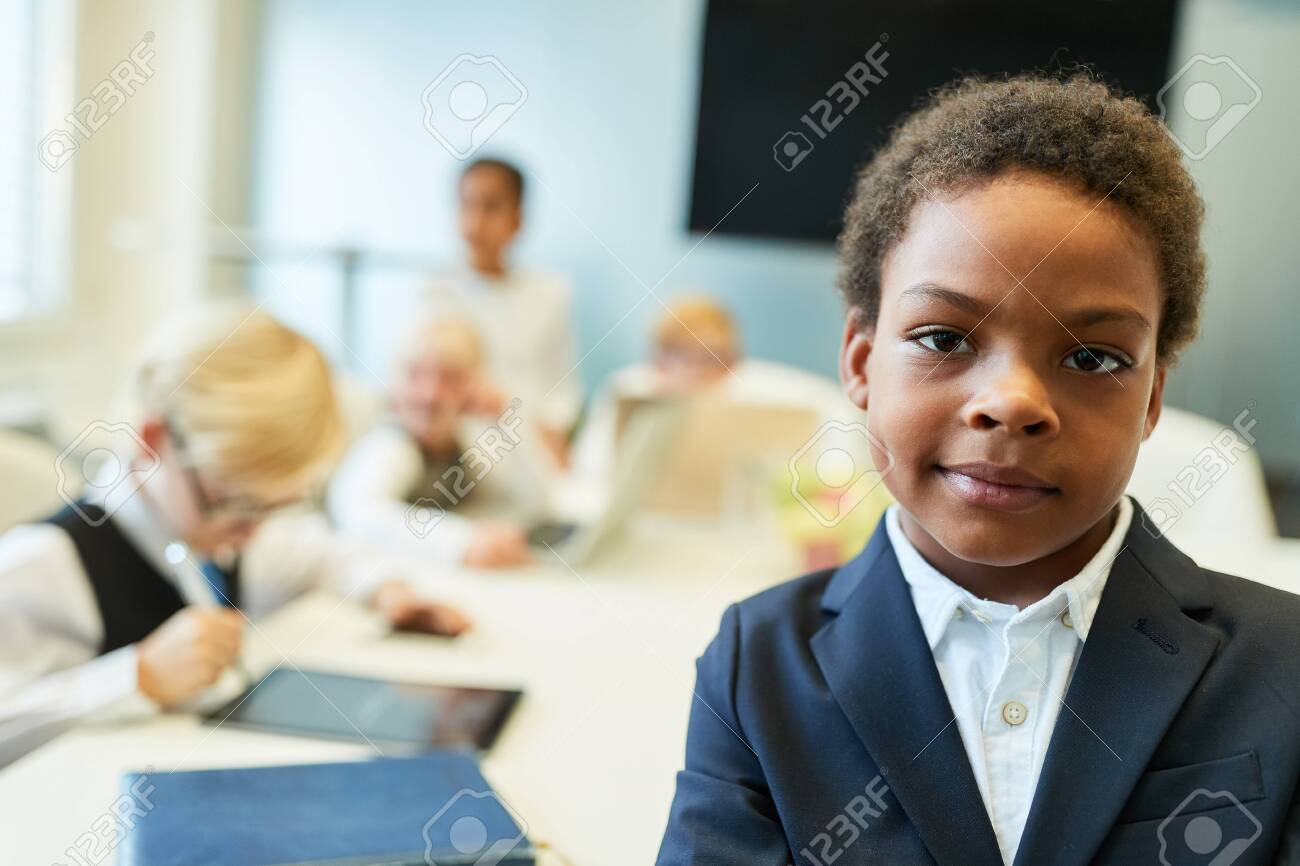 African child as a businessman or entrepreneur in front of his business team - 135173221