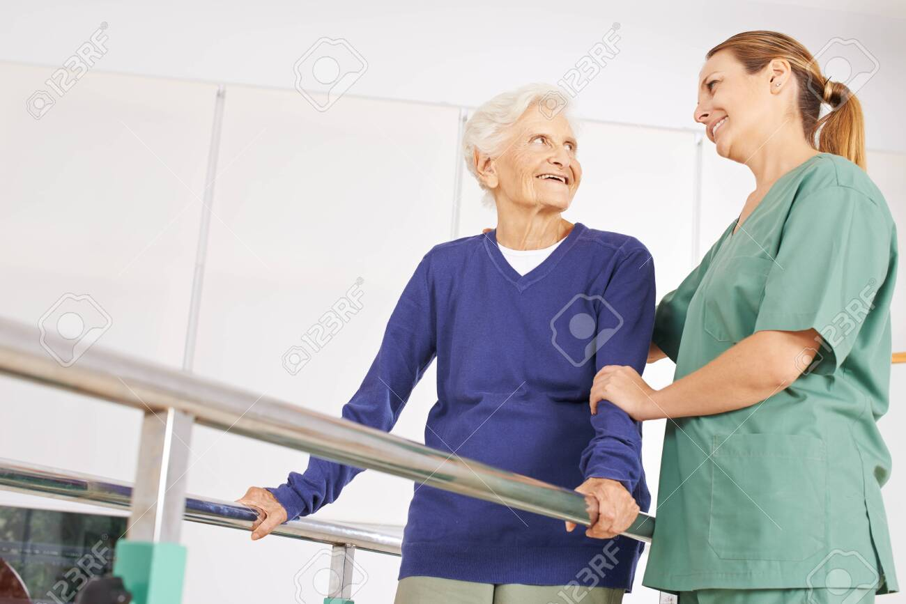 Old woman with physiotherapist at exercise therapy in nursing home - 136867805