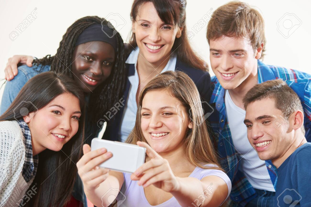 Laughing group of students takes a selfie with teacher together - 138550874