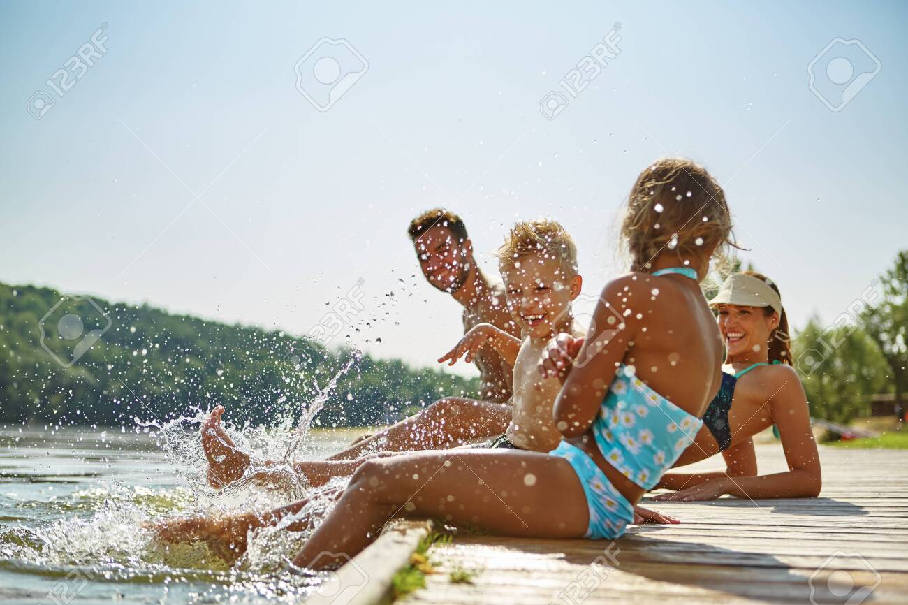 Happy family by the lake in summer holding feet in water - 139744900