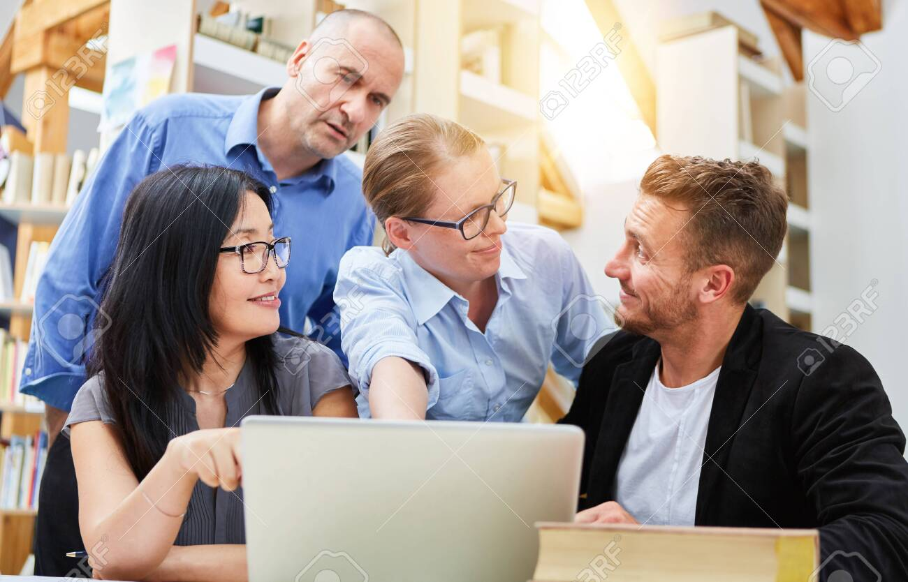 Software Developers in Business Startup Discussing in Front of Laptop Computer - 140701425