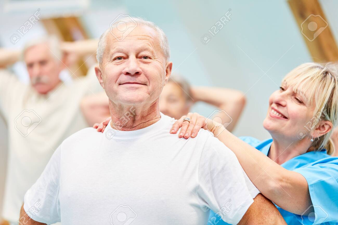 Therapist supports senior man in healthy back training - 144867465