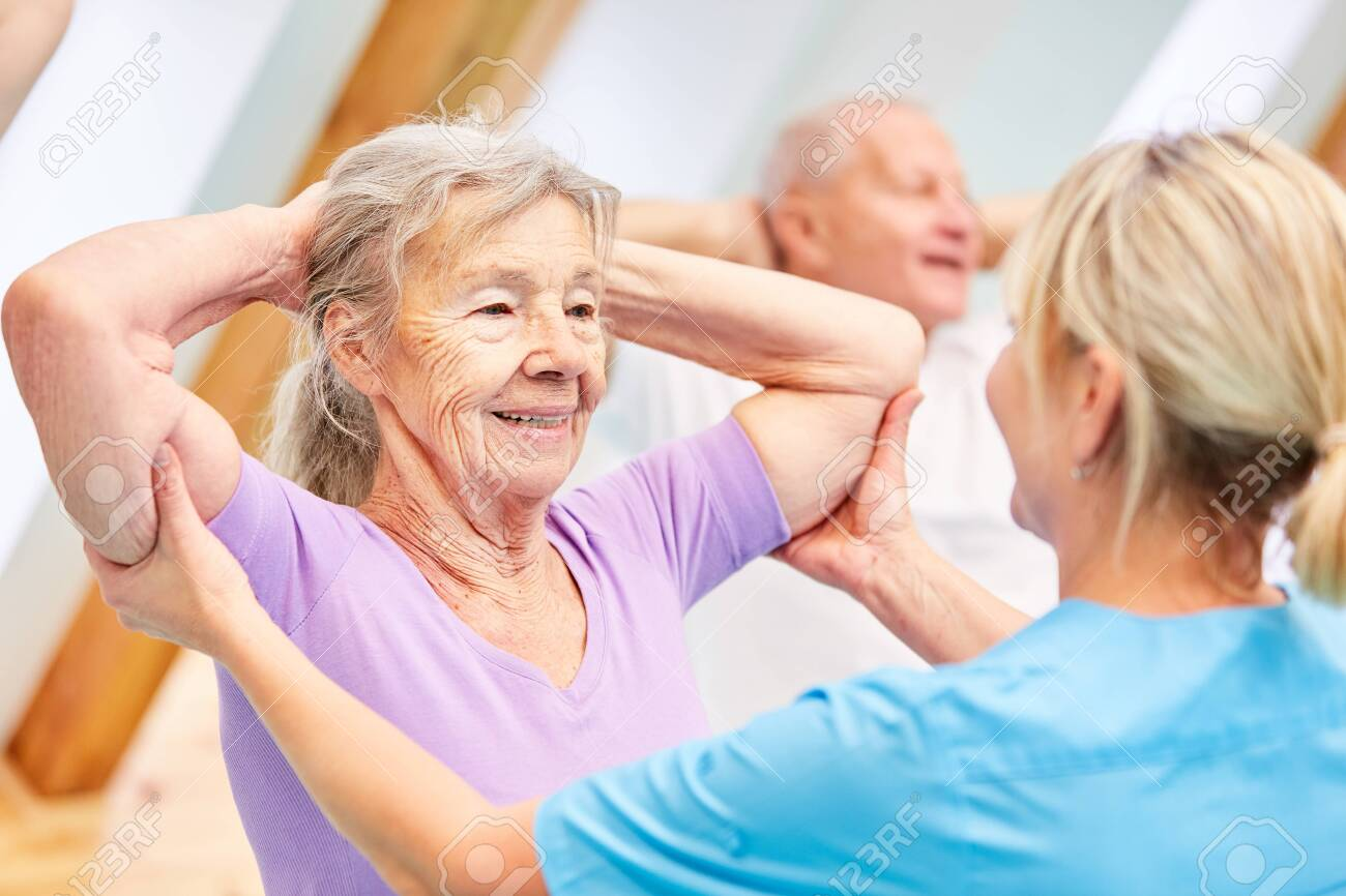 Trainer helps seniors with healthy back training in physiotherapy - 151488897