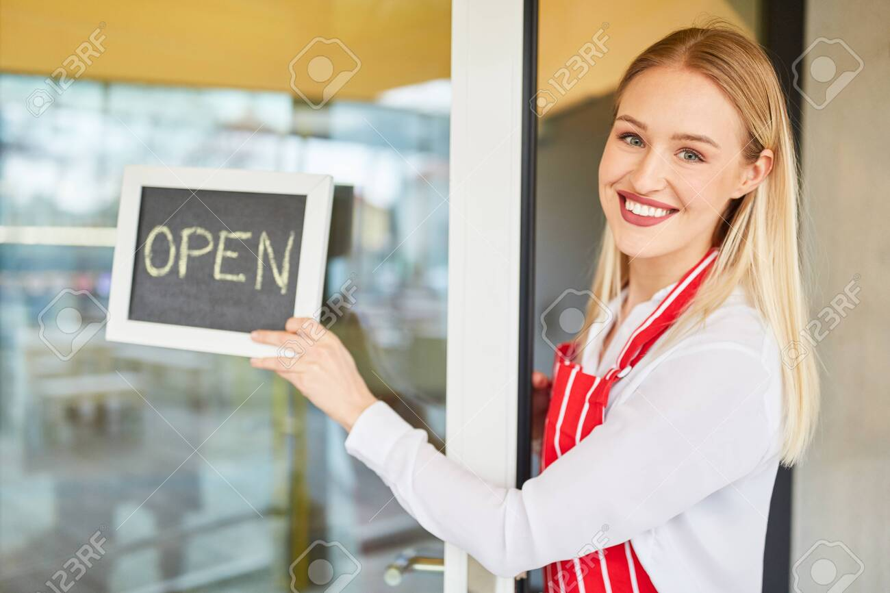 Young woman at the opening of her restaurant or bistro with chalkboard - 153001055