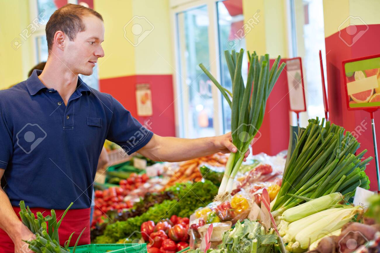 Smiling supermarket trainee fills up leek at the vegetable stall - 154530325