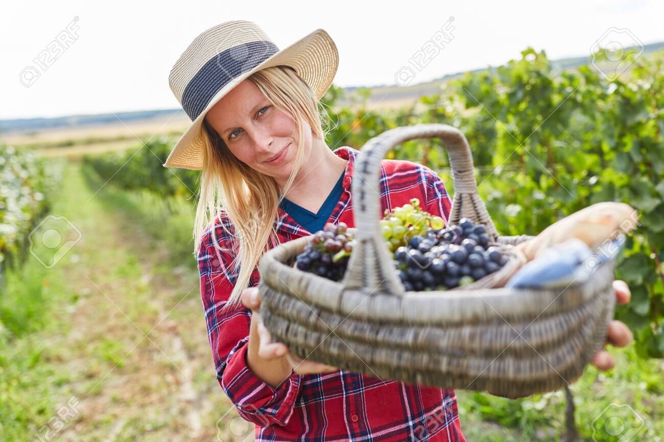 Young woman holding a picnic basket with red and white grapes - 155993377