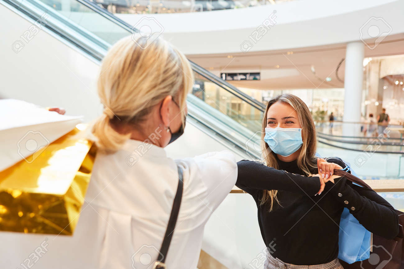 Two women with masks make elbows greeting in the shopping center at Covid-19 - 159015486