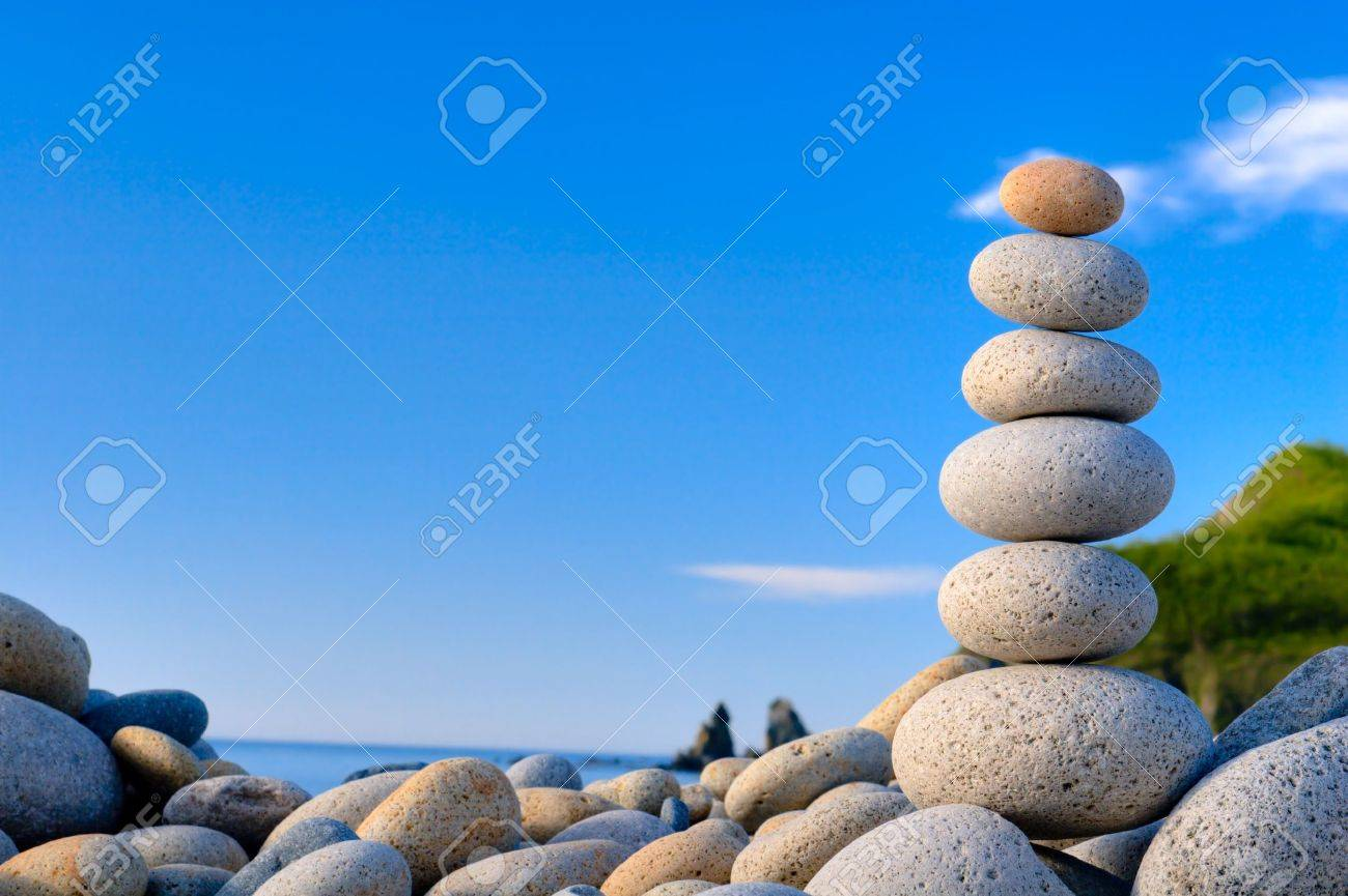 Round stones for meditation laying on seacoast - 12425030