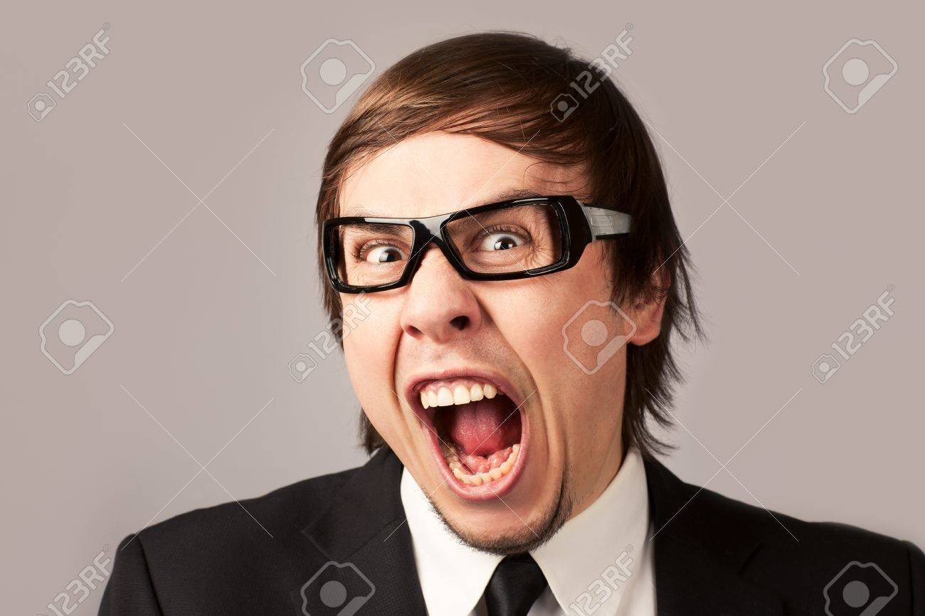 Close-up photo of screaming businessman, on a gray background - 12905288