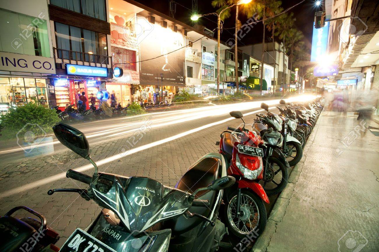 BALI - DECEMBER 27: Nighttime, mopeds stays in the parking at the shopping street, Kuta's area on December 27, 2012 in Bali, Indonesia. Kuta is known internationally for its long sandy beach, varied accommodation, many restaurants and bars. - 19739305