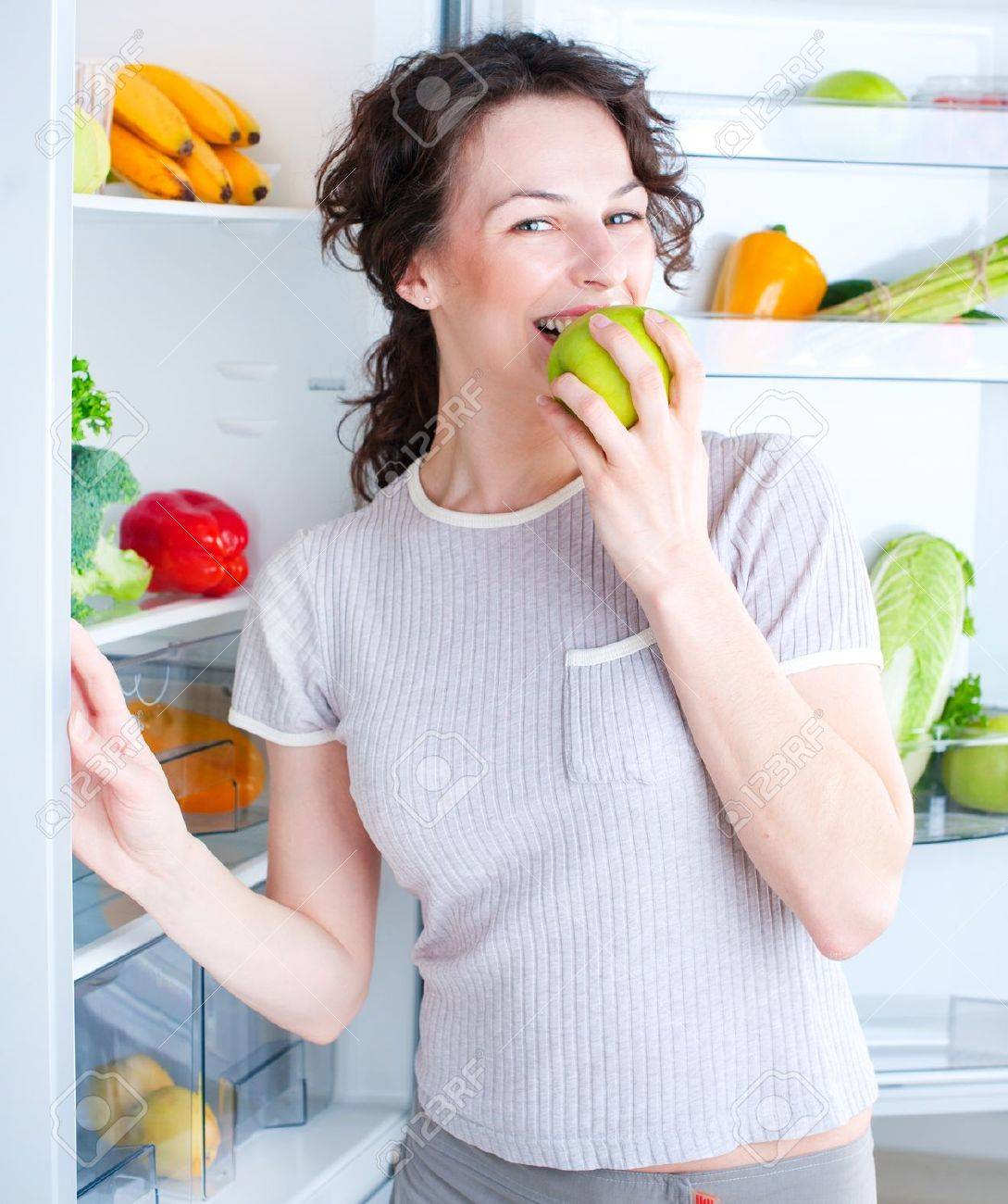 Beautiful Young Woman near the Refrigerator with fresh apple Stock Photo - 15044029