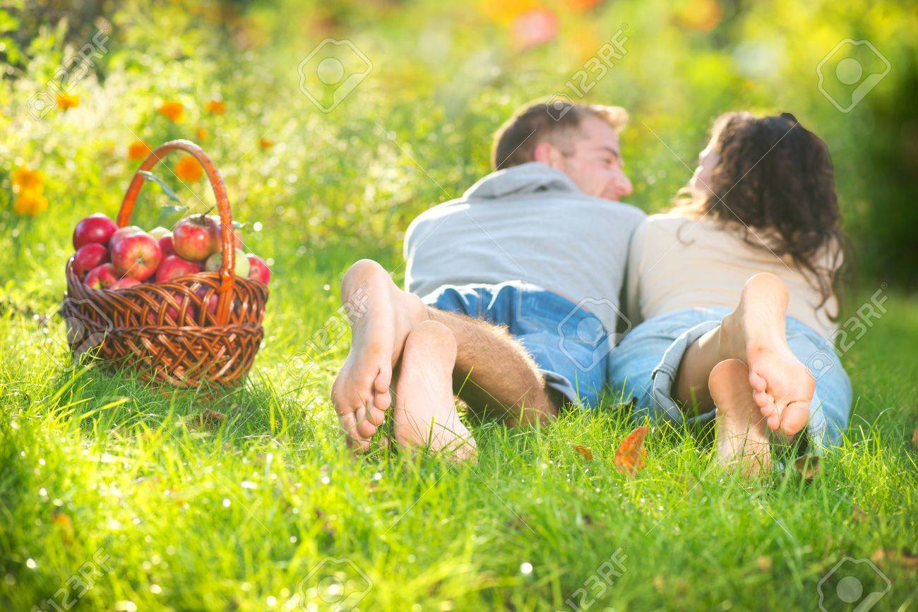 Couple Relaxing on the Grass and Eating Apples in Autumn Garden Stock Photo - 15658079