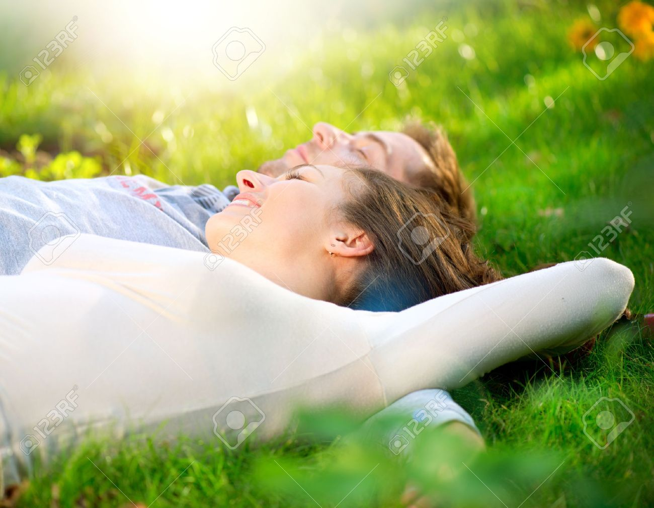 Young Couple Lying on Grass Outdoor Stock Photo - 15658051