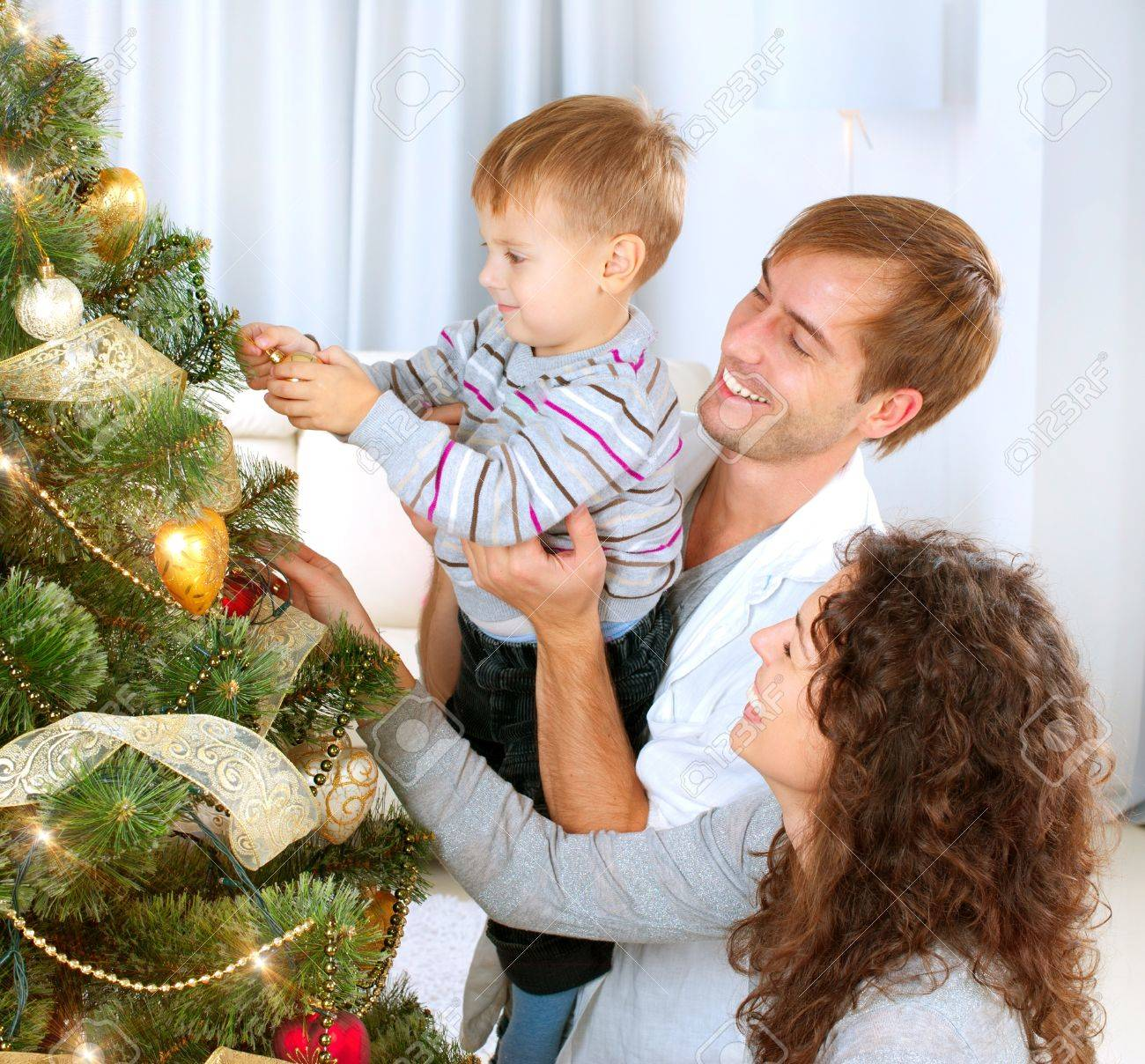 Young Family decorating a Christmas Tree Stock Photo - 16590126