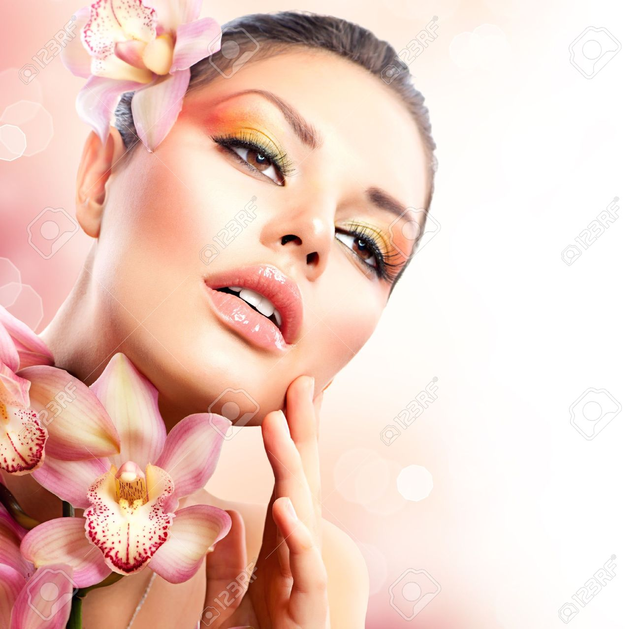 Beautiful Spa Girl With Orchid Flowers Touching her Face Stock Photo - 17383870