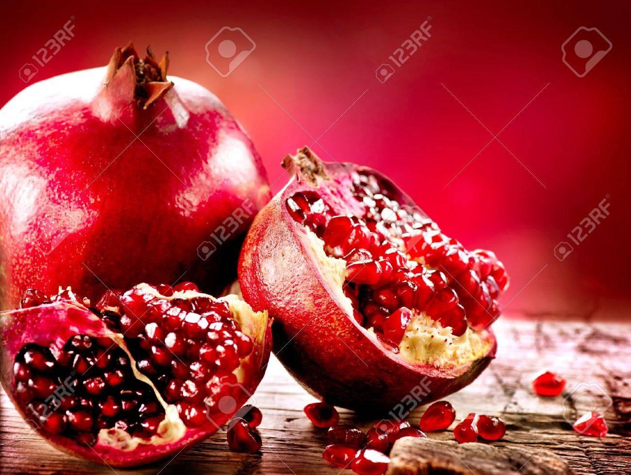 Pomegranates over Red Background Organic Bio fruits - 18697332