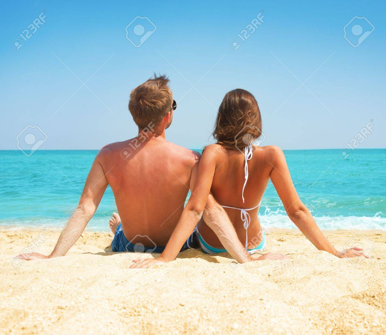 Young Couple Sitting together on the Beach  Vacation concept Stock Photo - 21289470