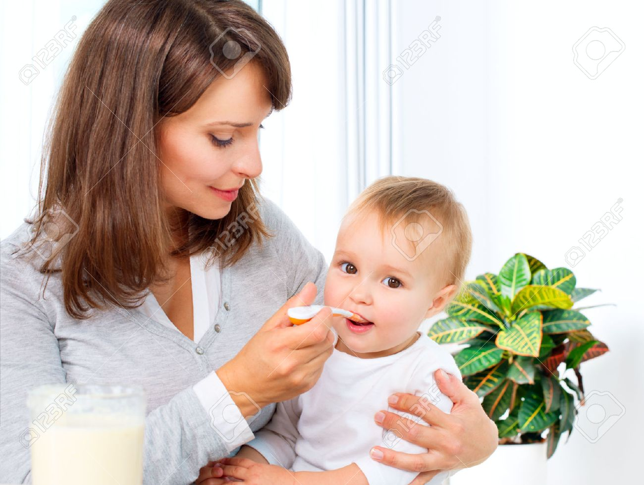 Mother Feeding Her Baby Girl with a Spoon Stock Photo - 22455290