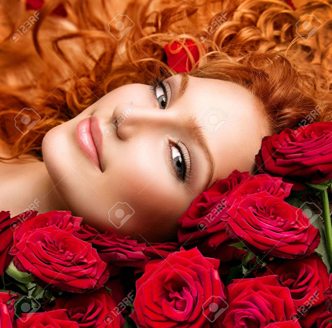 Woman with permed red hair and beautiful red roses Stock Photo - 29053669