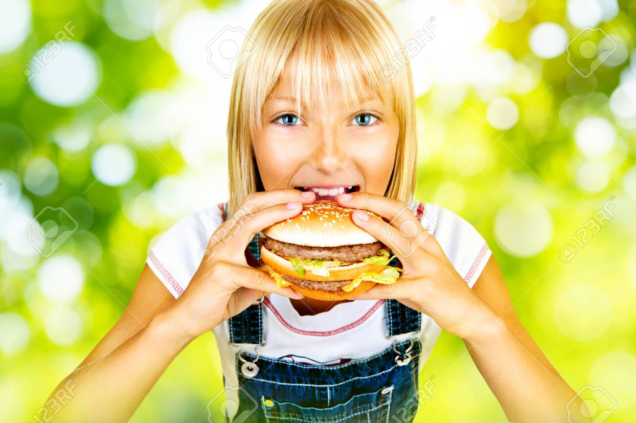 Pretty little girl eating a hamburger over nature background Stock Photo - 29917110
