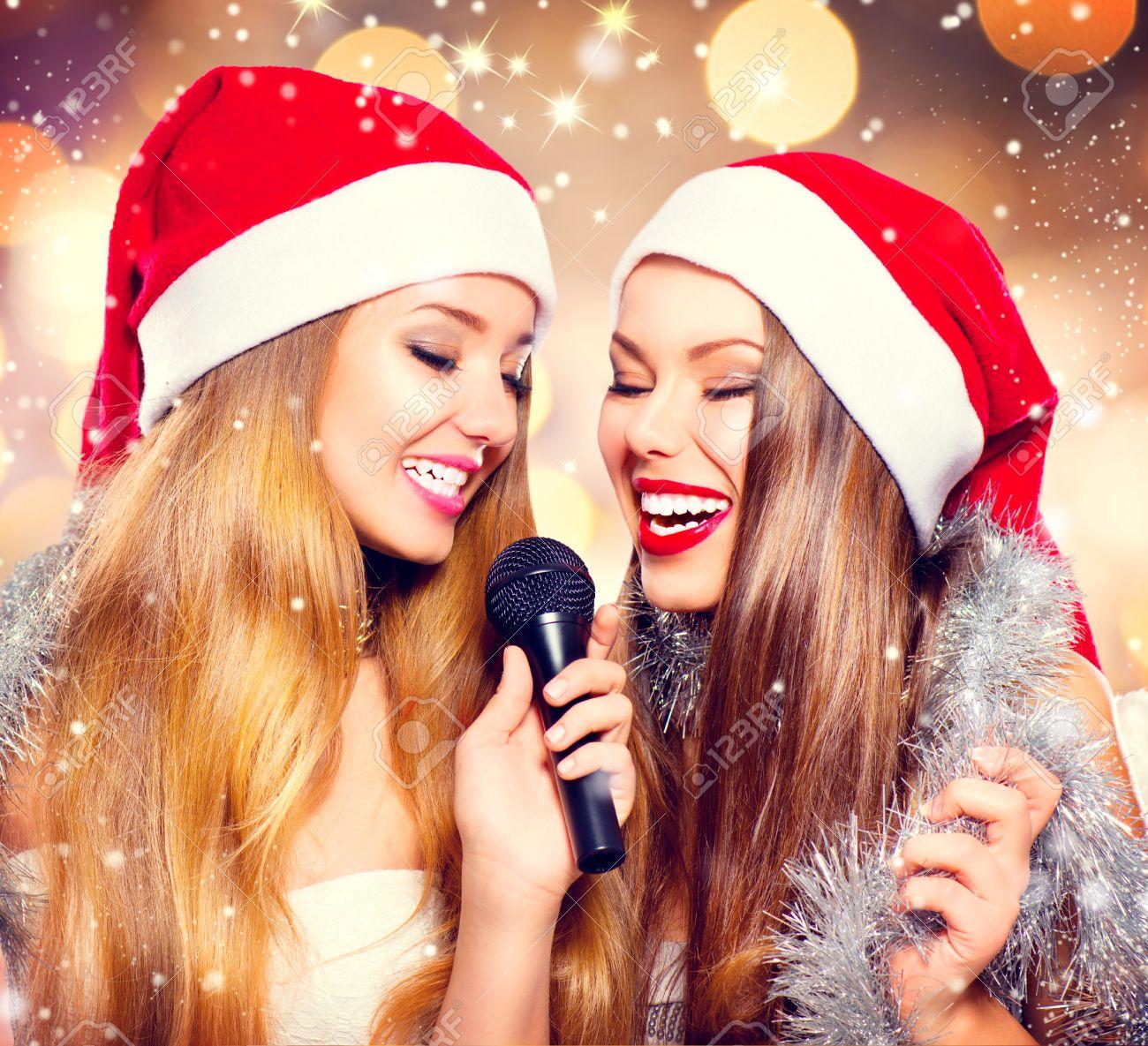 Christmas Party, Karaoke. Beauty Girls In Santa Hats Singing Stock ...