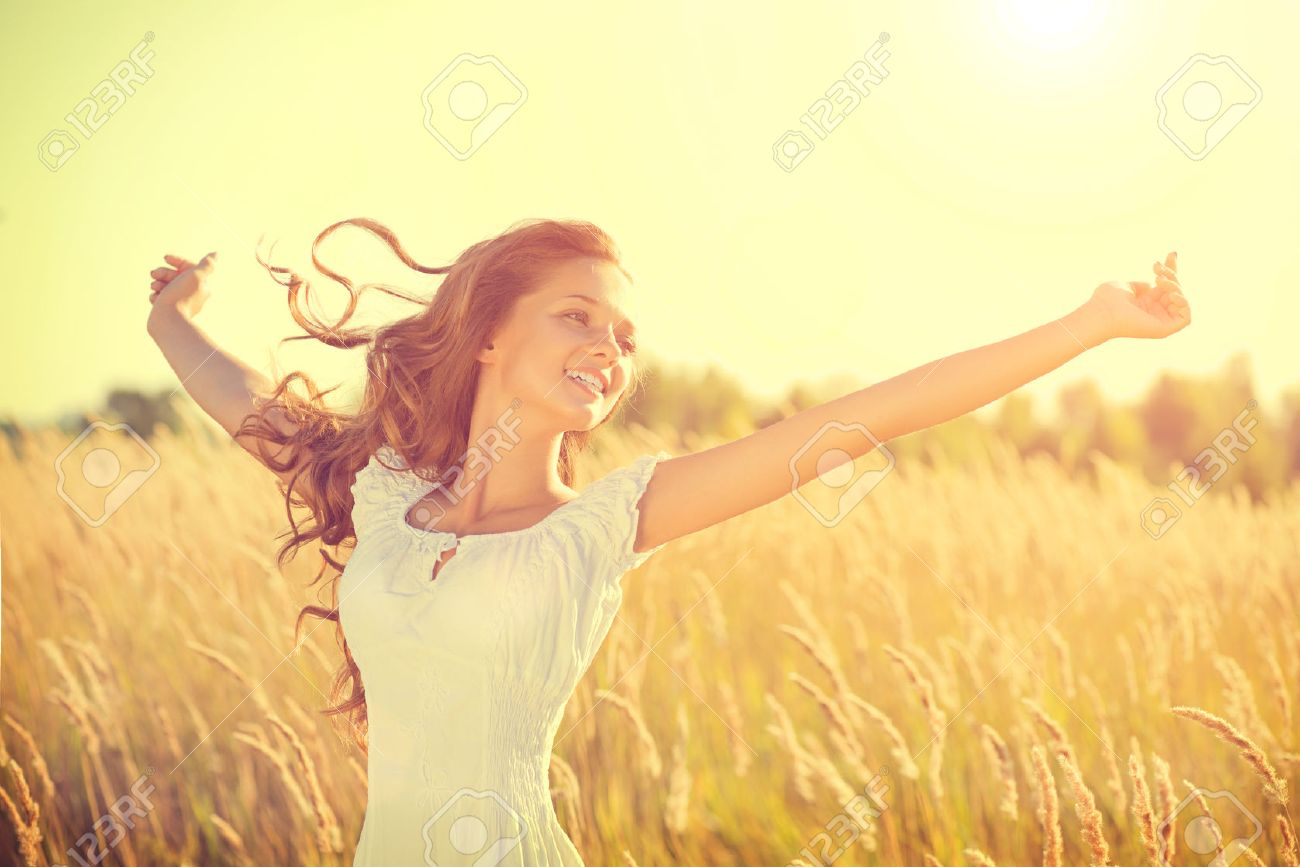 Beauty happy girl with blowing hair enjoying nature on the field - 34792225