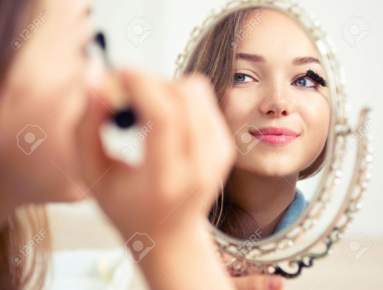 Beauty model teenage girl looking in the mirror and applying mascara - 42724222